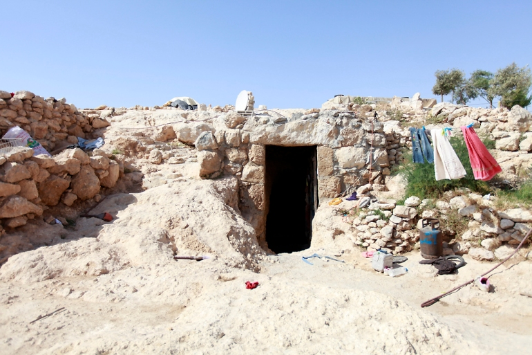 The typical entrance to the home is a stone doorway leading to a cave, which extends into the soft, clay-like rock. [Eloise Bollack/Al Jazeera]