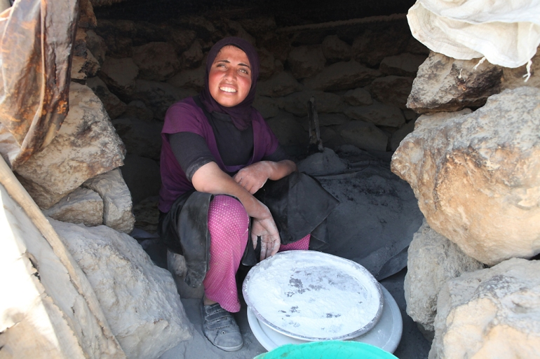 The daily portion of bread is prepared in the traditional taboon oven, a clay or stone oven built and used since pre-biblical times in the region. [Eloise Bollack/Al Jazeera]