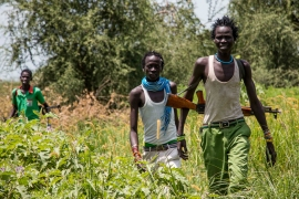 Young Nuer men carry their weapons through swamplands in South Sudan's traditional Nuer heartland of Waat, central Jonglei State. [Ashley Hamer/Al Jazeera]