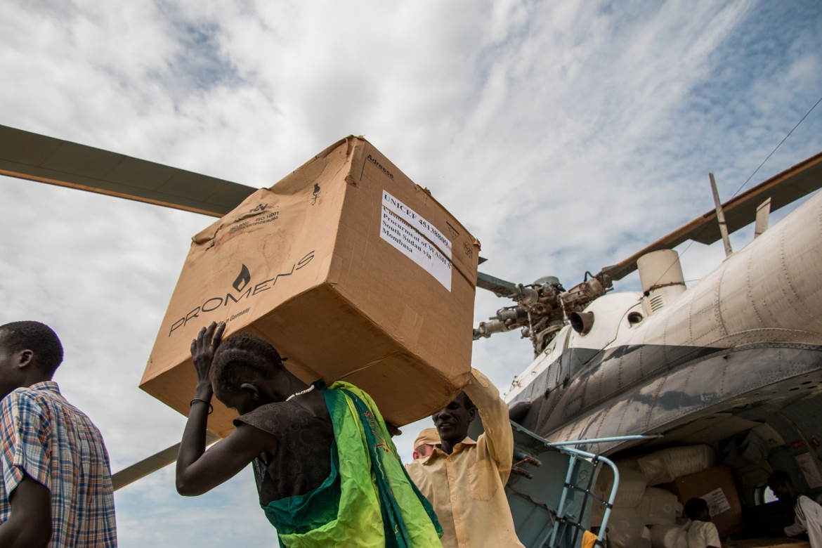 Men, women and children from the community help to unload supplies including vaccines, nutritional supplements, buckets, tarpaulins, water treatment products and building materials [Ashley Hamer/Al Jazeera]