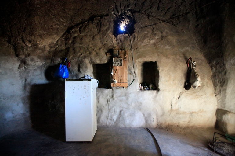 In the Jinba cave hamlet, walls are carved out and plastered, and chambers are dug out of the soft rock. The rozanna, a ventilation and light shaft also used to haul in grains for storage, was dug into the ceiling, and alcoves were cut into the walls to store belongings. [Eloise Bollack/Al Jazeera]
