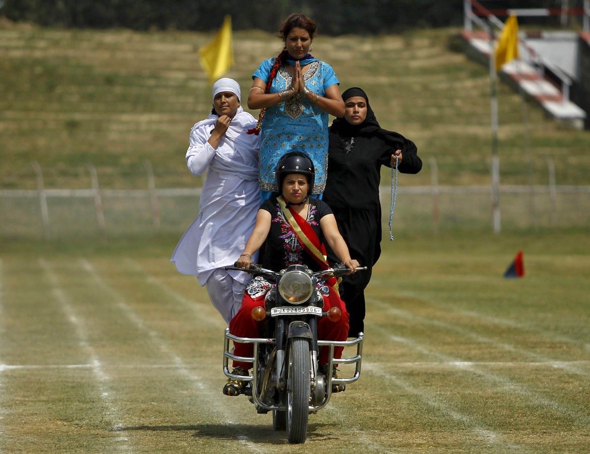 Indian policewomen, representing different religions, perform a stunt on a motorbike during the full-dress rehearsal for the Independence Day. [Danish Ismail/Reuters]
