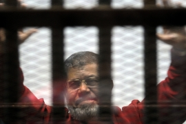 Mohamed Morsi has been appearing in court wearing the red prison uniform reserved for prisoners on death row [AP]