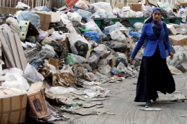 A woman walks past rubbish piled up along a street in Beirut, Lebanon [REUTERS]