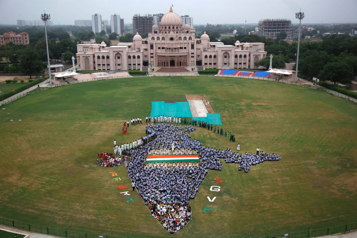 Indian students and teachers of Swaminarayan Gurukul form the map of India on the eve of Independence Day in Ahmadabad. [Ajit Solanki/AP]