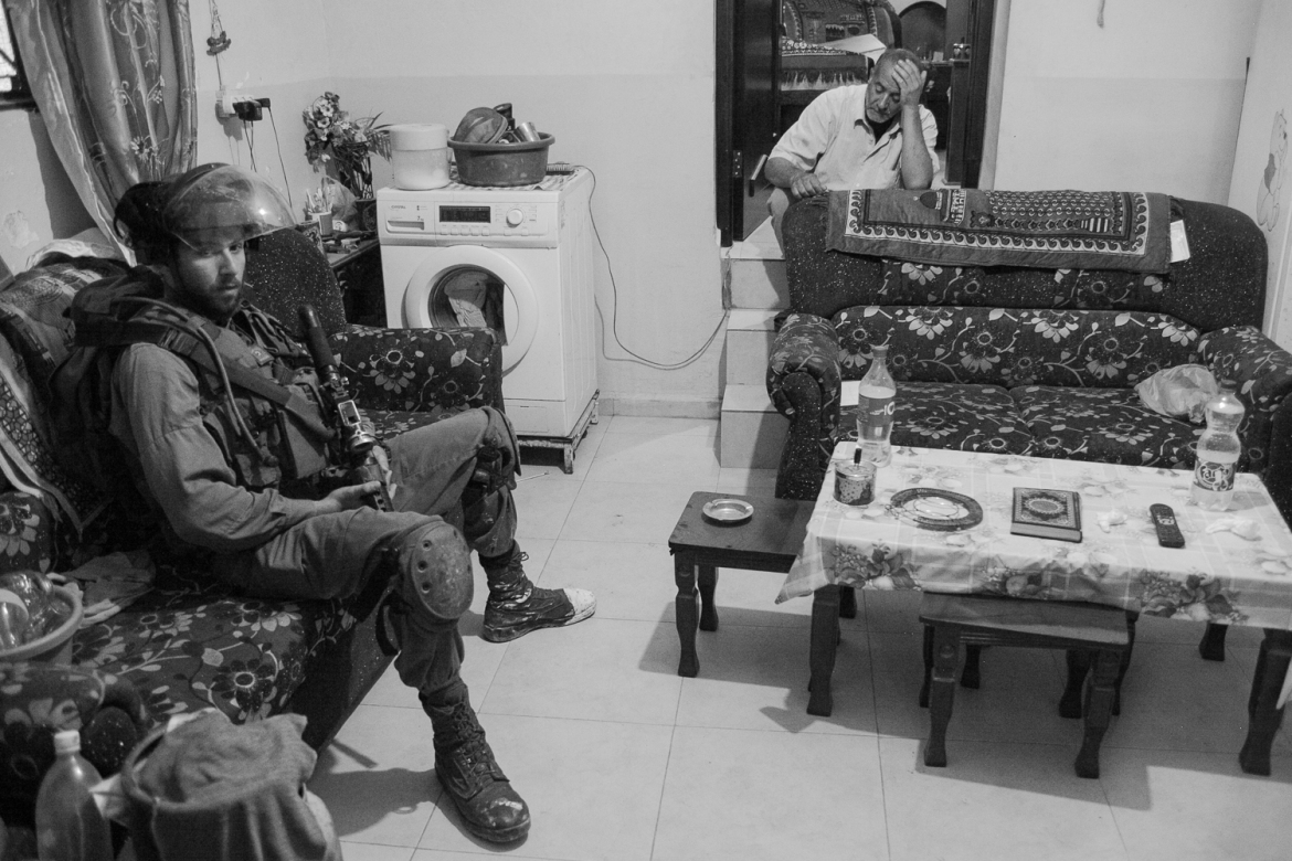 An Israeli soldier sits in Abed Abu Srour's home during a night raid. Asked about his work, the soldier said he was not proud of what he did. [Kelly Lynn/Al Jazeera]