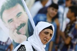A demonstrator holds a portrait of the PKK's jailed leader Abdullah Ocalan during a solidarity march in Diyarbakir, Turkey [Reuters]