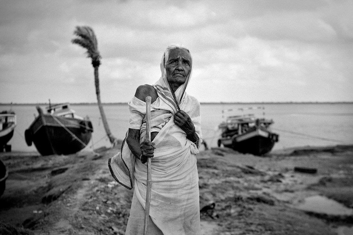 Chaya Mondal, 76, waits near the coastline, where the fishing trawlers would return at the end of day's catch. She has spent all her life on this vanishing Island. [Swastik Pal/Al Jazeera]