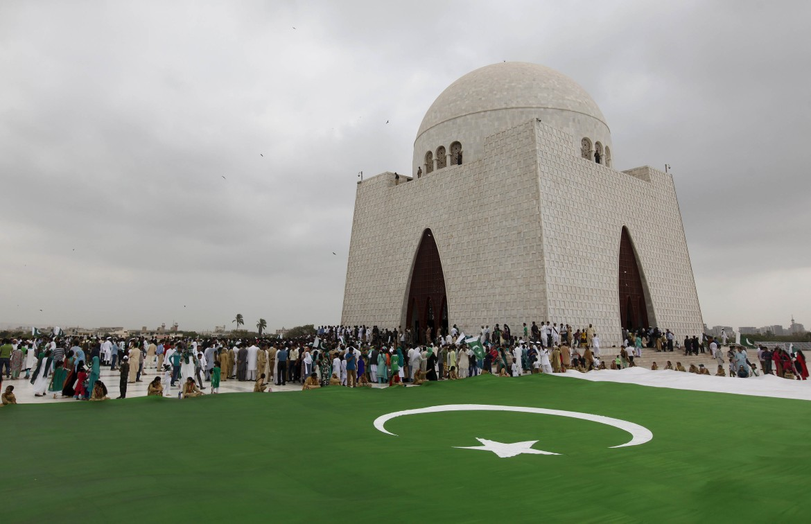 People gather near a national flag to celebrate the Independence Day at the mausoleum of Muhammad Ali Jinnah in Karachi, Pakistan. [Akhtar Soomro/Reuters]