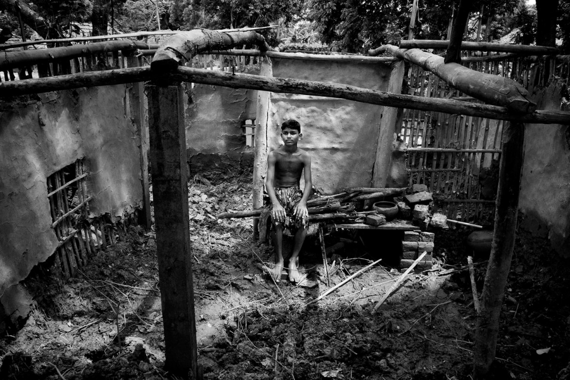 Suraj Jamal Mallick, 12, sits in front of his broken house. Every year, as the island shrinks, more people on the island become homeless as environmental refugees. [Swastik Pal/Al Jazeera]