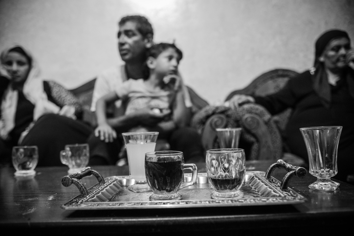 The family of Yaqoub Hammad, 21, sit in their home after he was arrested. Families typically gather after night raids to drink tea and decompress. [Kelly Lynn/Al Jazeera]