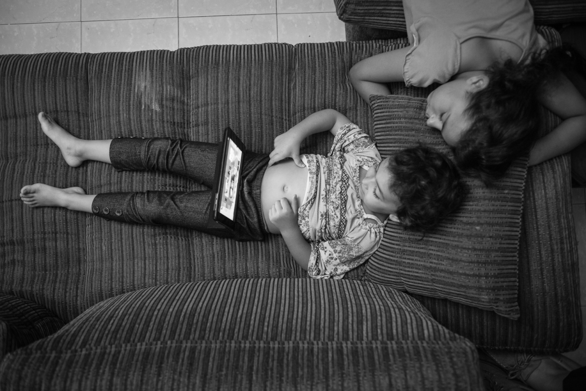 Three-year-old Jude and 11-year-old Ruweda play on an iPad around 5:30am after soldiers entered their building to arrest their cousin, Khaled al-Azzeh, from the apartment above. The girls show signs of anxiety from the constant military presence, including speech problems, aggression and difficulty sleeping, according to their family. [Kelly Lynn/Al Jazeera]