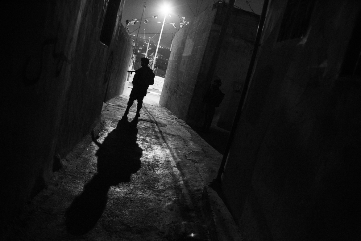 An Israeli soldier stands alone in an alleyway in al-Azza Refugee Camp, while the rest of his unit searches a home. [Kelly Lynn/Al Jazeera]