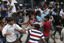 Migrants clash outside the Kos police station, which was closed on a public holiday [Reuters]