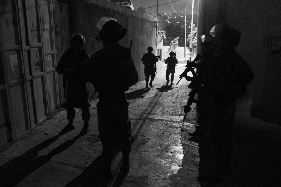 Israeli forces prepare to scale a wall in the nearby al-Azza refugee camp during a night raid. Youth are often targeted during raids for alleged stone throwing, an offence now punishable by up to 20 years in prison. [Kelly Lynn/Al Jazeera]