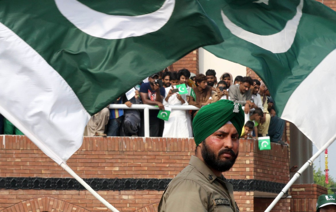 A Pakistani Border Ranger waves the flag during the celebrations to mark Independence Day. [Rahat Dar/EPA]