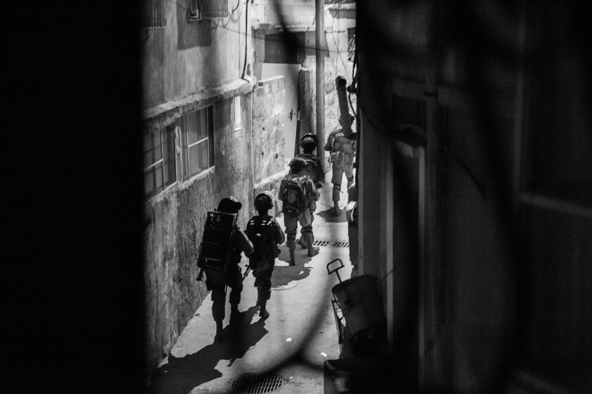 Israeli soldiers walk through a narrow street in the Aida camp. Aida is known throughout Bethlehem as a gathering spot for Palestinian youth to confront Israeli forces, who occupy a military base on the opposite side of the separation wall that flanks the community. [Kelly Lynn/Al Jazeera]