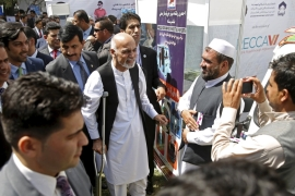 Ghani talks to participants at an exhibition of Afghan products in Kabul [REUTERS]