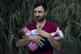 A Syrian refugee feeds his daughter after they arrived on a dinghy, from Turkey to Lesbos island, Greece [AP]