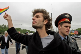 A gay rights activist is detained by a police officer in Moscow during a pro-LGBT demonstration [Alexander Zemlianichenko/AP]