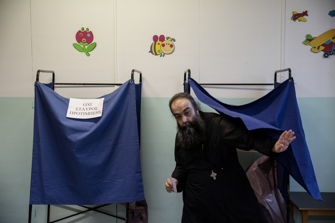 A greek orthodox priest is exiting a voting cabin, after casting his ballot in a polling station in Thessaloniki. [Konstantinos Tsakalidis/SOOC]