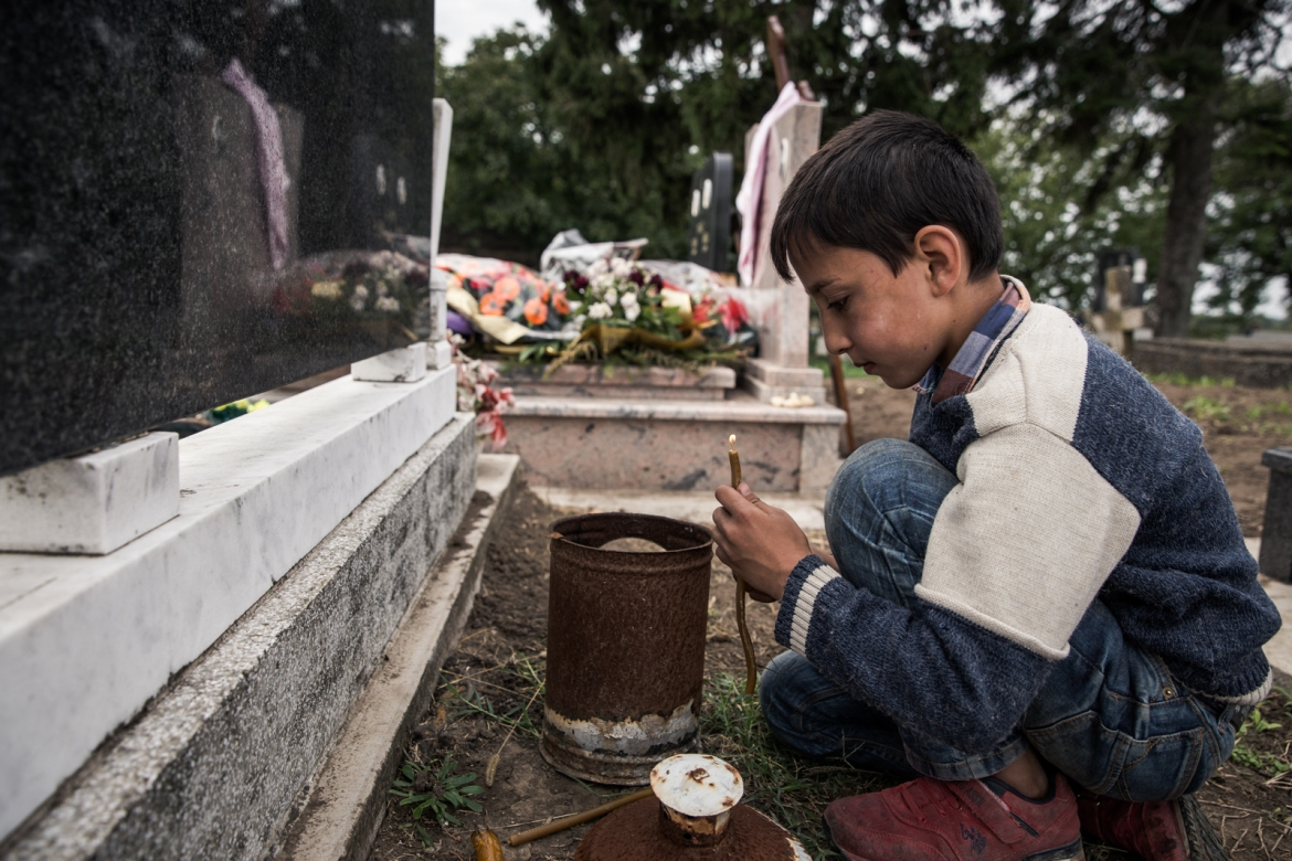 A Muslim refugee boy lights candles in a graveyard in the area between the checkpoints in the Serbian town of Sid and Tovarnik in Croatia. His father says it is because they respect all religions. [Ioana Moldovan/Al Jazeera]