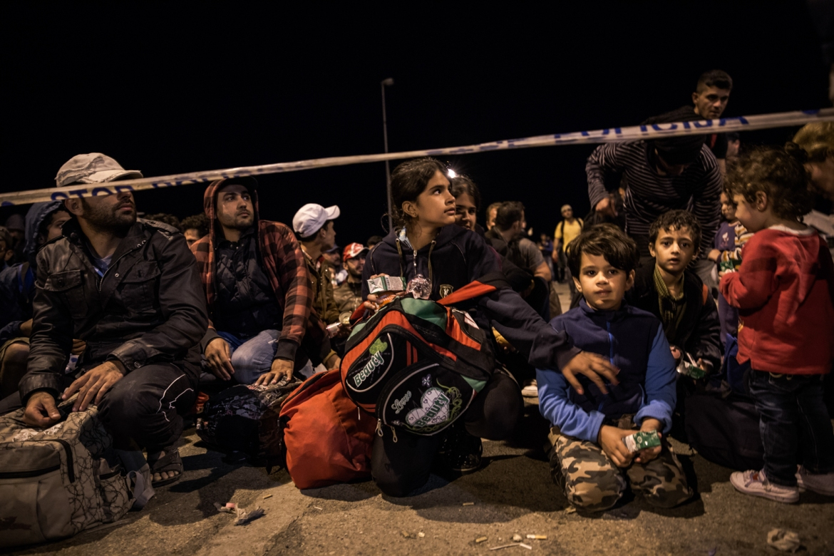 Refugees waiting behind the police line to get onto the buses and out of the border crossing. [Ioana Moldovan/Al Jazeera]