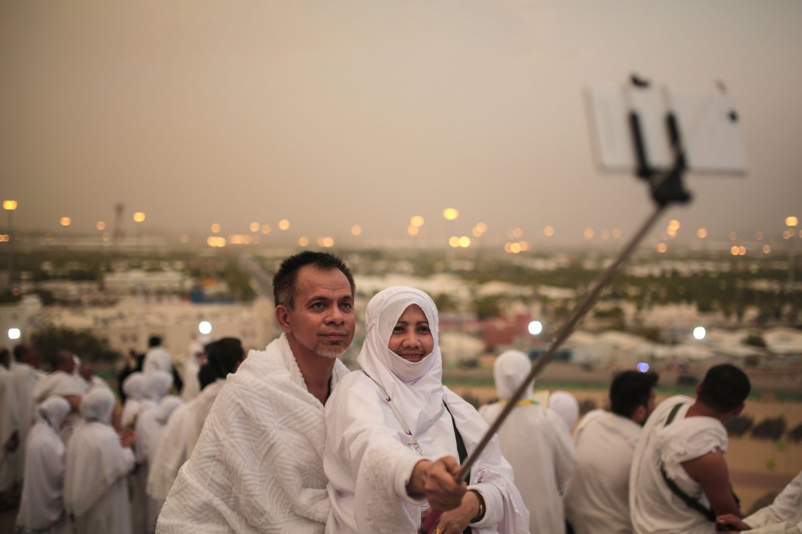 A Muslim pilgrim couple take a selfie on a rocky hill called the Mountain of Mercy, on the Plain of Arafat, near the holy city of Mecca. [Mosa ab Elshamy/AP]