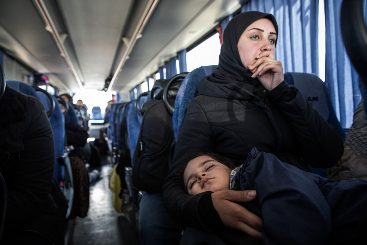 A refugee woman with her child waiting in the bus outside of Opatovac camp. UNHCR has been working with Croatian authorities to provide decent conditions for the refugees in the camp. [Ioana Moldovan/Al Jazeera]