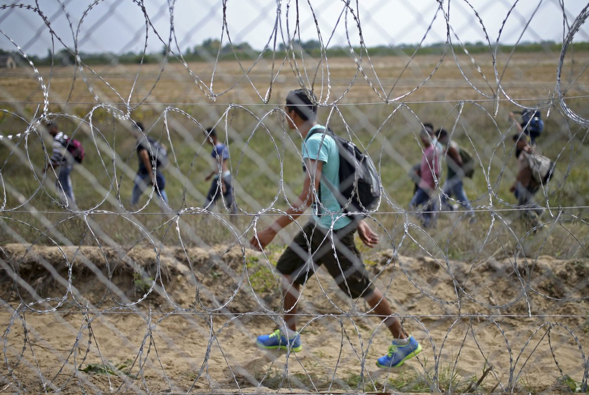 Hungary is set to introduce harsher border-control laws that would send smugglers to prison and deport refugees who cut under its new razor-wire border fence [Dado Ruvic/Reuters]