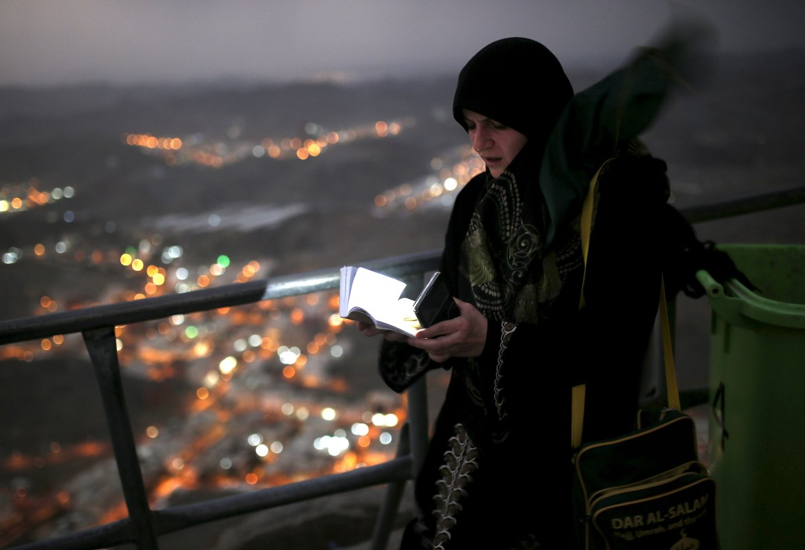 A Muslim pilgrim uses her mobile phone to light up as she reads from the Quran after visiting Hera cave, where Muslims believe Prophet Mohammad received the first words of the Koran through Gabriel, at the top of Mount Al-Noor. [Ahmad Masood/Reuters]