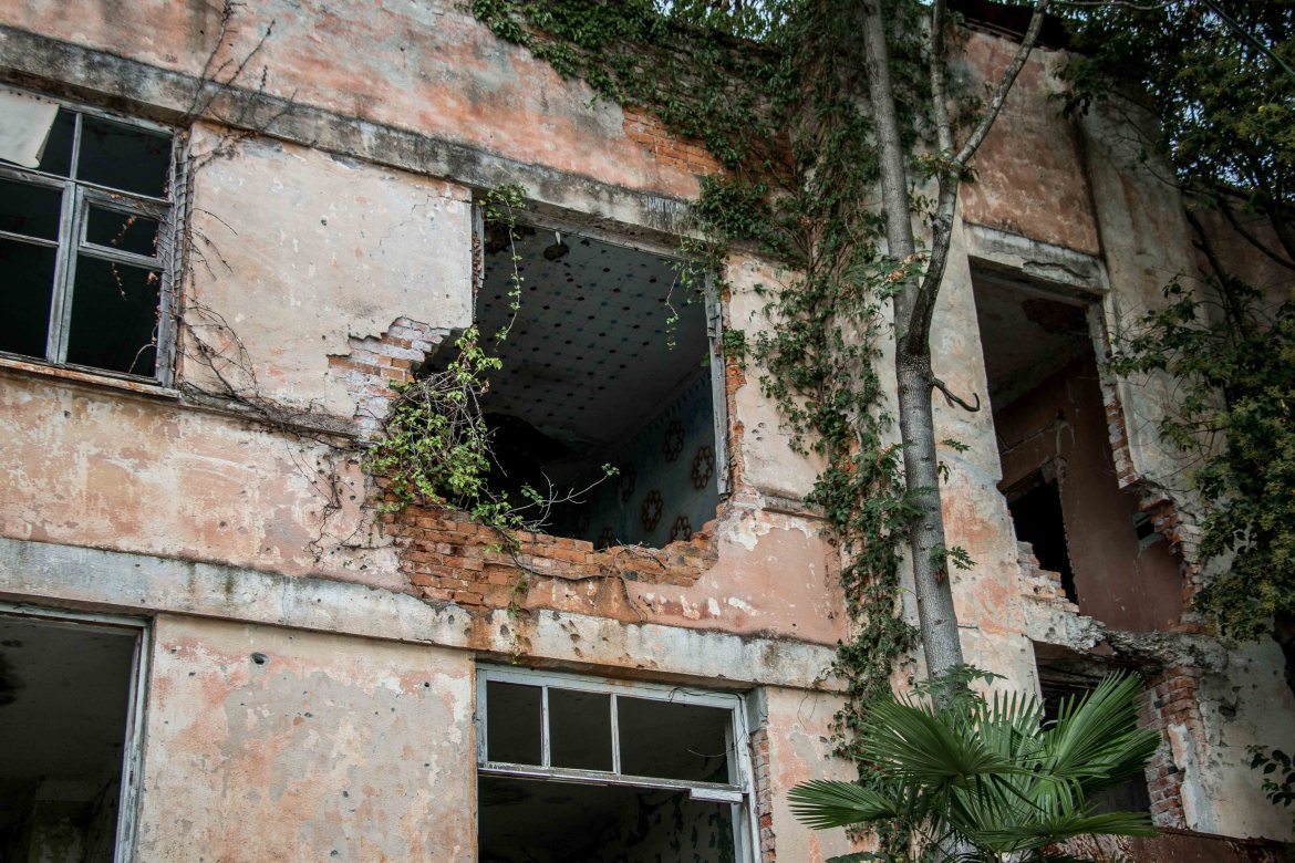 Damaged buildings throughout Sukhumi - some abandoned, others still occupied - have stood for 20 years with the pits and blast holes of conflict. [Al Jazeera]