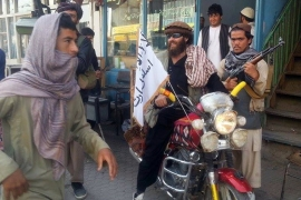 A Taliban fighter sits on his motorcycle adorned with a Taliban flag in a street in Kunduz [AP]