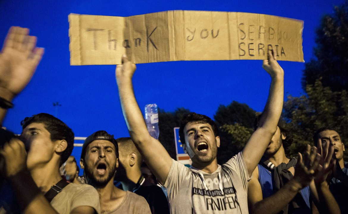 Refugees hold a sign reading: ''Thank You Serbia'' as they gather at a closed border crossing between Serbia and Hungary [Balazs Mohai hungary Out/ EPA]