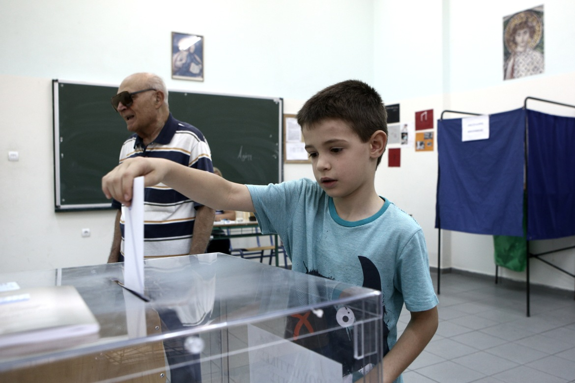 A child casting a vote on behalf of his grandfather. [Nick Paleologos/SOOC]