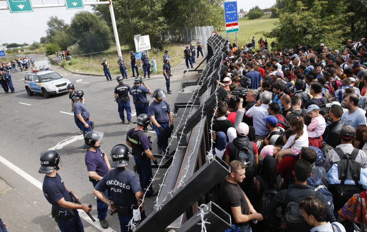 Hundreds of refugees pressed against a barrier erected by Hungarian police across a main highway linking Serbia and Hungary on Tuesday [Marko Djurica/Reuters]