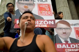 Demonstrators hold defaced campaign posters of presidential hopeful Manuel Baldizon as they demand election reform in Guatemala City on Saturday [Moises Castillo/AP]