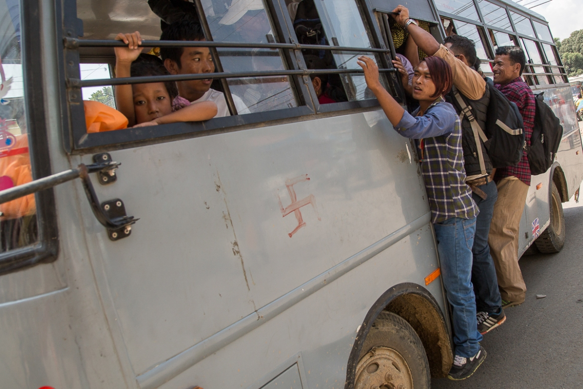 Residents overload a bus as public transportation is affected by the petrol crisis. [Omar Havana/Al Jazeera]