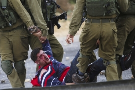 Members of the Israeli armed forces detain a wounded Palestinian protester during clashes [EPA]
