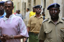 Ali Kololo, left, a former employee of the Kiwayu Safari village, is escorted by police to prison after he was sentenced to death [Reuters]