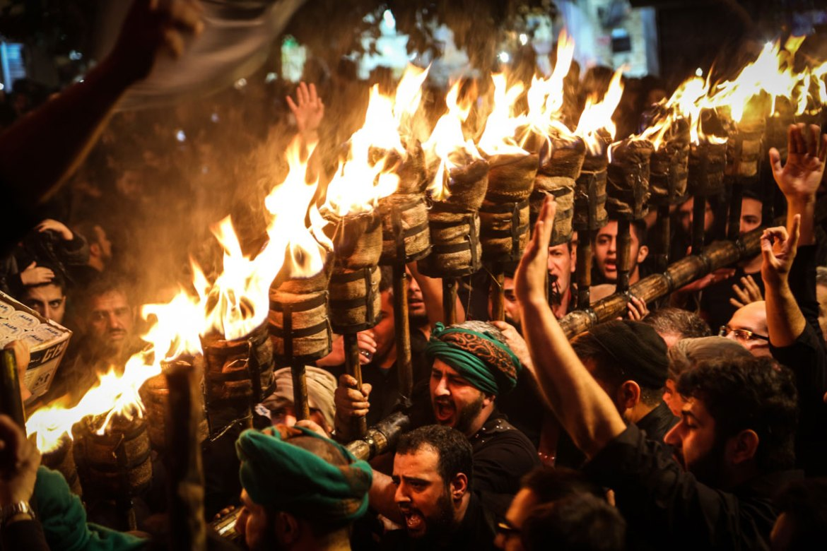 While carrying the torch, or Mashaal, the men sing the song of mourning, called Nohe. [Mohammad Ali Najib/Al Jazeera]
