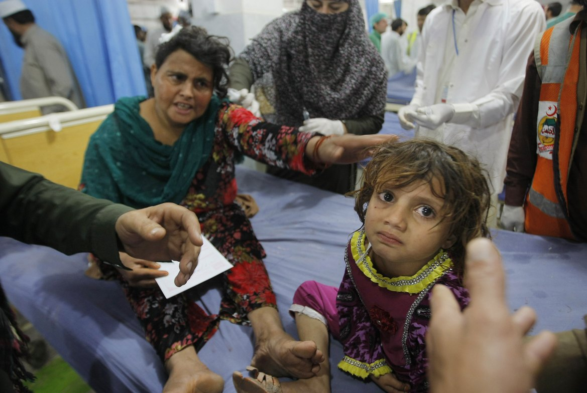 A Pakistani mother waits for treatment with her daughter at a local hospital in the city of Peshawar. [Mohammad Sajjad/AP]