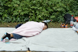 A refugee boy sleeps outside the Berlin Office of Health and Social Affairs [Fabrizio Bensch/Reuters]