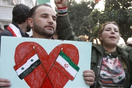 A protester holds a placard showing the Iranian and Syrian flags during a demonstration in front of the Iranian embassy in Damascus [AP]