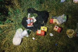 Clothes and foodstuffs lay discarded at the side of a track cutting through fields, between the Serbian and Croatian border, where a group of Syrian refugees crossed the border at night. [Phil Moore/Al Jazeera]