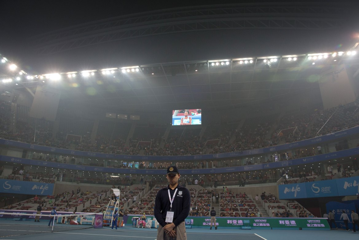 A security stands guard at the stadium shrouded with pollution haze during a singles match between Ana Ivanovic of Serbia and Venus Williams in Beijing. [Andy Wong/AP]