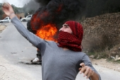Palestinian protesters throw stones at Israeli soldiers during clashes in the West Bank city of Hebron [EPA]