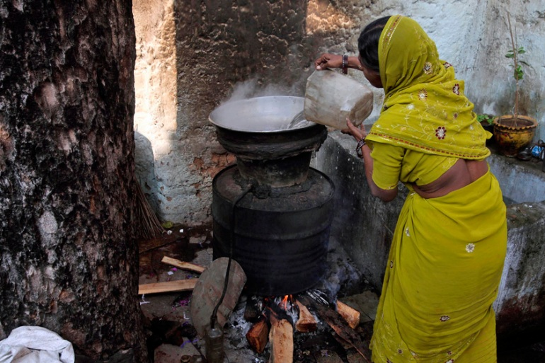 An Indian woman prepares Gudumba, local illicit liquor in the southern Indian state of Andhra Pradesh [Mahesh Kumar A/AP]