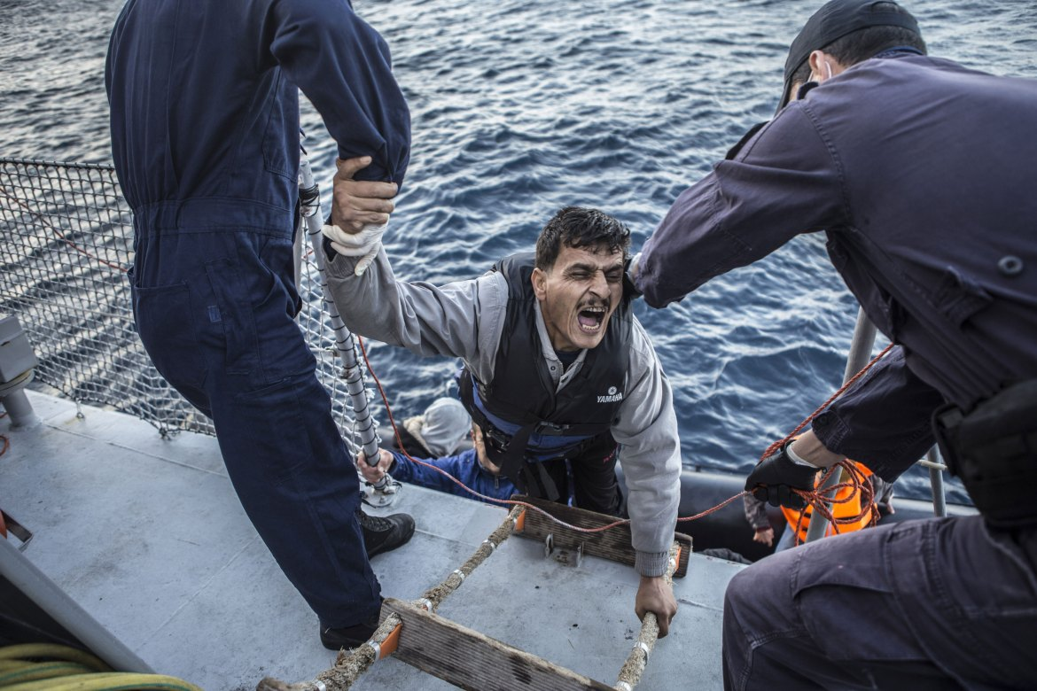 An Afghan man, whose legs are so cold and numb he can no longer walk, is helped aboard by crew members. [Anna Pantelia/Al Jazeera]