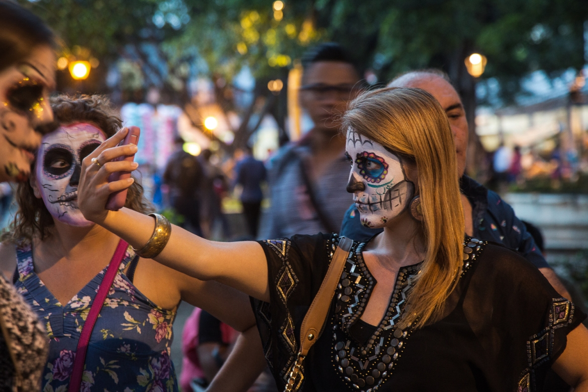 A young woman takes a selfie after getting her face painted at the Zocalo. But face painting is not a traditional feature of the Day of the Dead celebrations in Oaxaca, and some locals worry that the recent influx of tourists has introduced new elements to the traditional festivities. [Gabbi Campos/Al Jazeera]